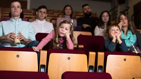 Child is bored watching movie in cinema house