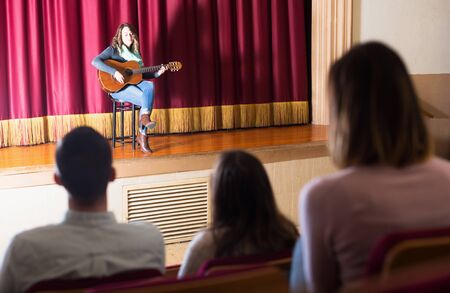Adult audience listening to beauty guitar concert in concert hall Stock Photo - 129243301