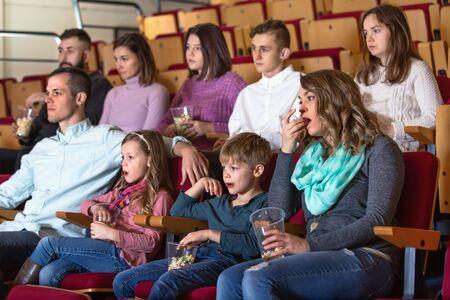 Number of charming cheerful people enjoying film screening and popcorn in cinema Фото со стока - 129243302