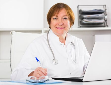 Smiling woman doctor working effectively in her office Stock fotó