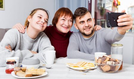 Cheerful family spending time together at home, taking selfie with phone