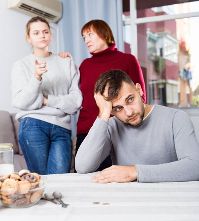 Portrait of chagrined guy sitting separately having problems in relationship with family
