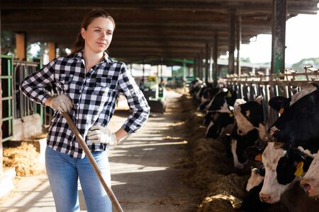 Portrait of active female employee working in cowshed on farm