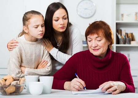 Dissatisfied woman with daughter gazing at her mother writing letter at home