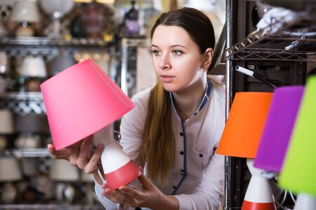 Young woman choosing new lamp on table in furniture store Stok Fotoğraf - 129258017