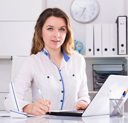 Portrait of young female in the office sitting at the table Zdjęcie Seryjne - 129258056