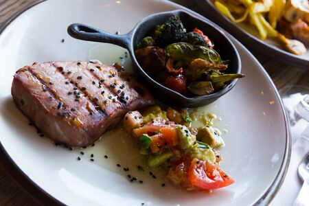 Healthy dinner, braised tuna fillet with grilled vegetables and salad of fresh tomatoes and avocado