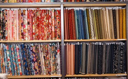 View of cloth rolls of different colors and patterns on shelves in fabric store
