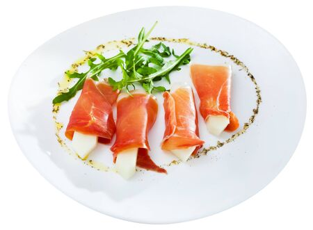 Spanish tasty dish rolls of prosciutto di parma with melon served with arugula at plate, close up. Isolated over white background