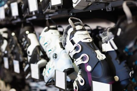 Different new  stylish models of boots for alpine skiing on shelves in shop