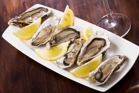 Seafood appetizer fresh oysters with lemon on white plate
