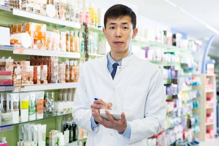 pharmacist is inventorying medicines with notebook near shelves in apothecary.