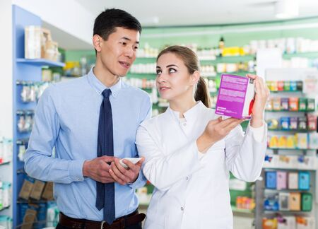 Female specialist is helping male client choose prescription medicine in pharmacy.