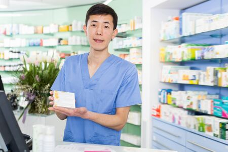 Positive an pharmacist is standing with medicines near cash box in pharmacy