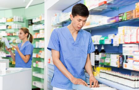 Positive  diligent  man pharmacist is searching medicine in drawers in apothecary.
