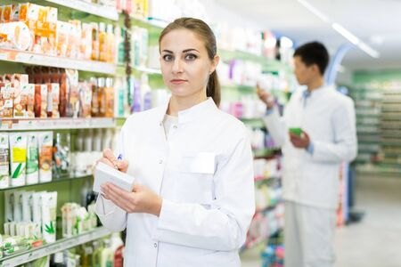 Young woman is checking medicine with notebook in shelves in apothecary