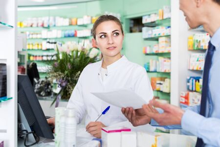 Female pharmacist is helping male client choose medicine near cash box in drugstore