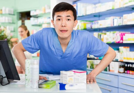 Portrait of chinese cheerful  man pharmacist who is standing on his work place near cashbox in apothecary.