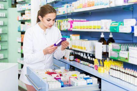 Woman specialist is attentively looking medicines in lockers in drugstore Stok Fotoğraf - 130589872