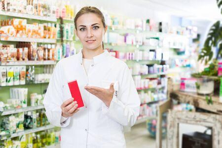 Farmacéutico de mujer sonriente está de pie con medicamentos en farmacia Foto de archivo
