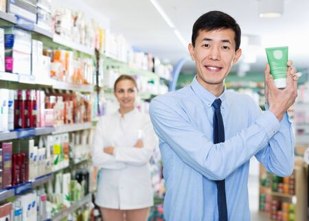 Portrait of glad  positive  client who is satisfied of recommended medicines in pharmacy.