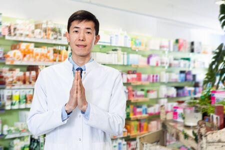 Portrait of chinese cheerful  smiling man pharmacist who is standing on his work place in apothecary.
