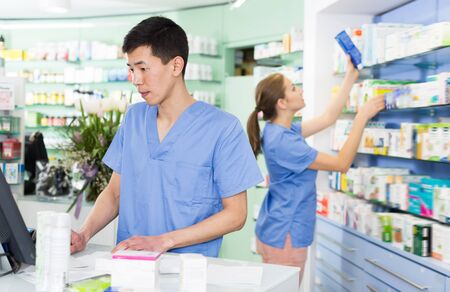 Handsome man pharmacist is standing with medicines near cash box in pharmacy Stok Fotoğraf - 130591789