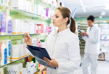 Female specialist is attentively stocktaking medicines with notebook near shelves in pharmacy