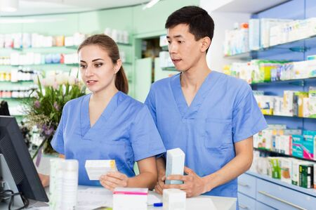 Portrait of two pleasant smiling pharmacists who are standing on their work place near table with cashbox in apothecary. Stok Fotoğraf - 130594229