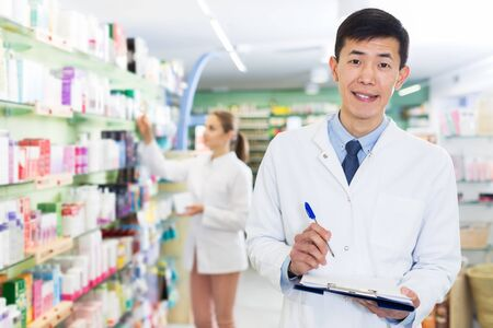 Male pharmacist is attentively stocktaking medicines with notebook near shelves in pharmacy Stok Fotoğraf
