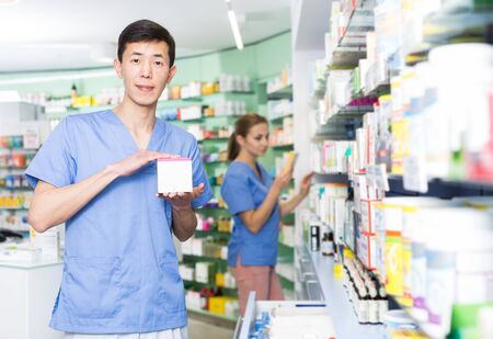 Portrait of  male pharmacist standing with medicines in medical shop
