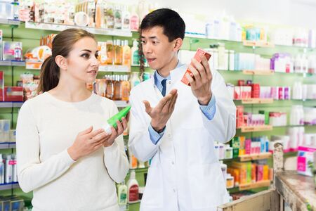 smiling positive pharmacist is recommending medicine for young woman client in apothecary.