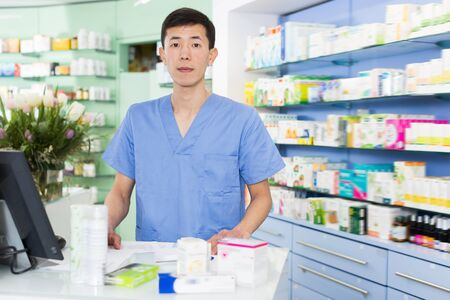 Happy pharmacist is standing with medicines near cash box in pharmacy Stok Fotoğraf - 130598505