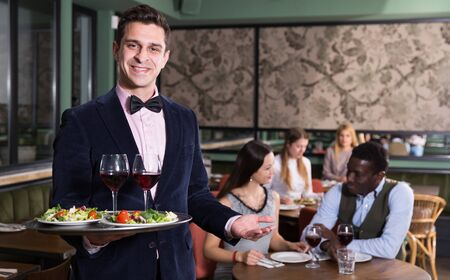 Handsome elegant waiter with serving tray welcoming to restaurant