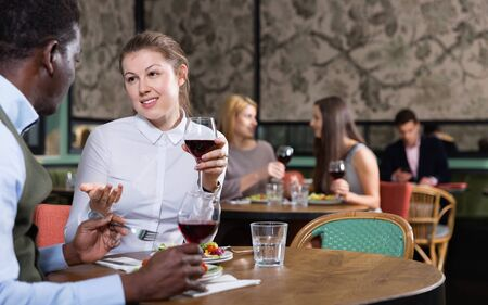 Young smiling  woman with African American colleague on friendly meeting over dinner with wine in restaurant Stock fotó