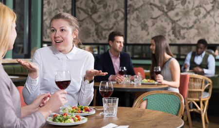 Happy attractive girl emotionally discussing with female friend while dining in cozy restaurant
