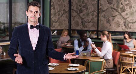 Polite confident waiter inviting to visit modern urban restaurant