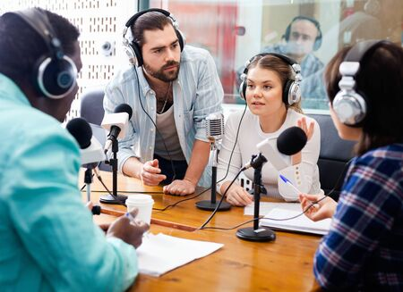 Scandal interview. Two young outraged guests answering questions of cheerful friendly radio hosts during live radio show