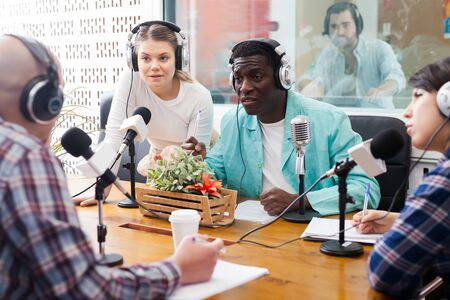 Glad presenters of different nationalities in sound broadcasting station hosting live radio show