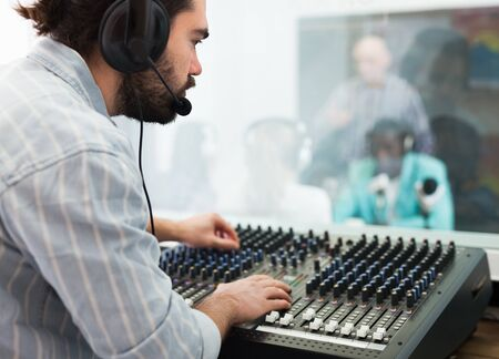 Focused bearded guy engaged in sound engineering, working at audio control panel in radio studio