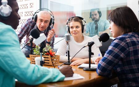 Multinational group of cheerful glad friendly   adults emotionally discussing in radio studio