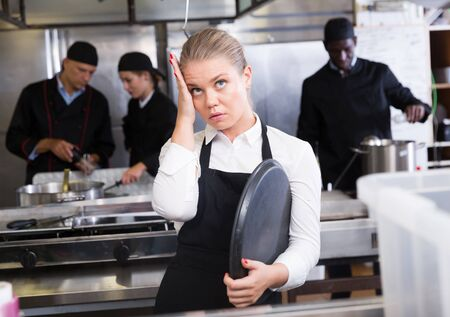 Young waitress expressing dissatisfaction and disappointment with not cooked ordered meals in restaurant kitchen