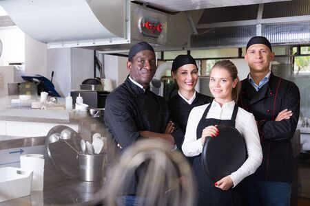 Portrait of confident smiling team of chefs in interior of restaurant kitchen