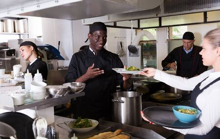 Confident African-American chef checking ordered dishes in kitchen of restaurant before serving guests Zdjęcie Seryjne