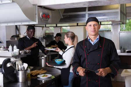 Portrait of confident male chef in restaurant kitchen with busy professional staff