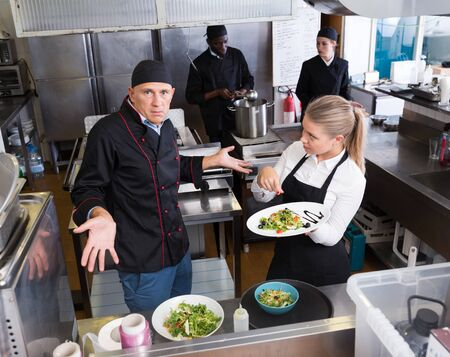 Bewildered chef making helpless gesture while talking with surprised waitress pointing to cooked dish Stock fotó