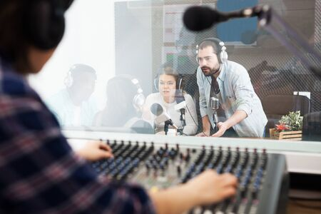 Young presenters in sound broadcasting station hosting live radio show. View from room where audio engineer controlling sound on air