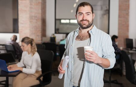 Portrait of cheerful male entrepreneur during daily work in modern office with coworkers