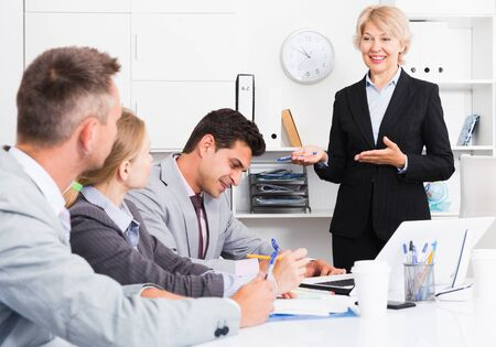 Confident businesswoman explaining to workgroup business plans in office