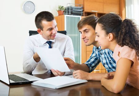 Smiling young family couple and banking agent discussing possibility of mortgage